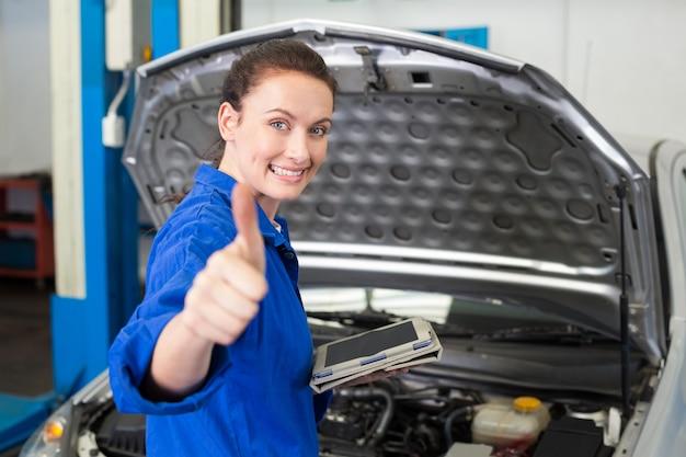 Mécanicien à l'aide de tablette pour réparer la voiture
