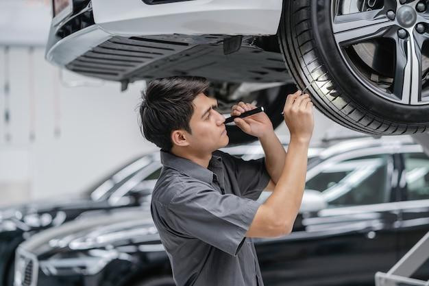 Mécanicien asiatique contrôle des pneus et du flambeau dans un centre de maintenance qui fait partie de la salle d'exposition
