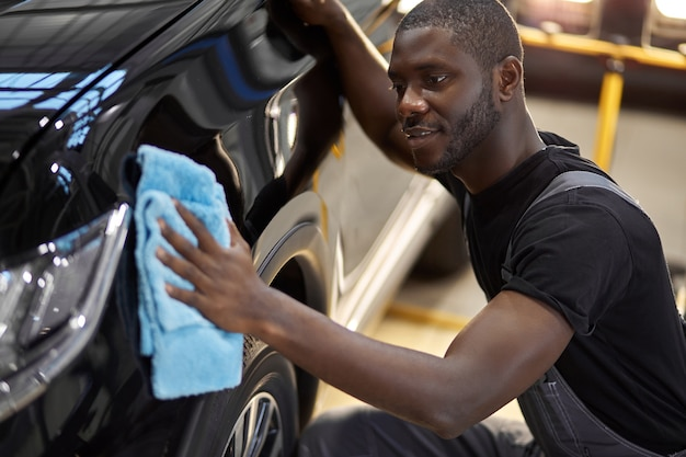 Un mécanicien automobile afro-américain essuie la surface parfaite de la machine après le polissage