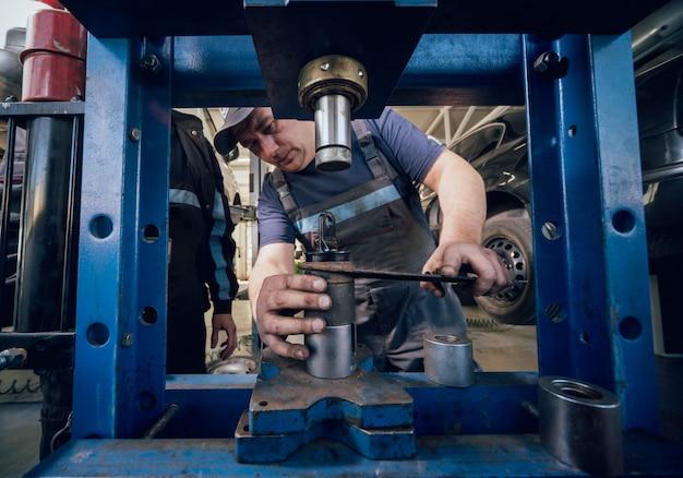 Mécanicien automobile appuyez sur nouveau silentblock à la station-service de réparation. service auto.