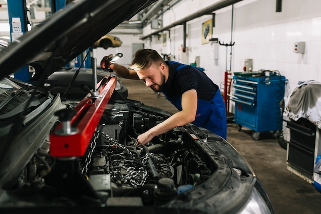Mécanicien automobile attrapant le moteur de la voiture