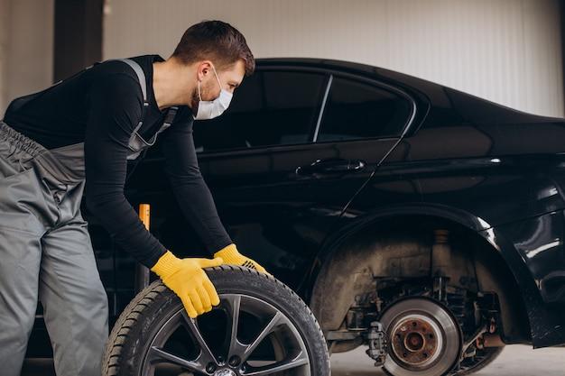Mécanicien automobile changeant les roues en voiture