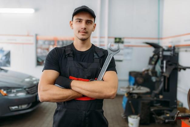 Mécanicien automobile avec clé, industrie de service de pneus ou entreprise. technicien répare un pneu de voiture dans un garage, inspection automobile professionnelle en atelier, travail de réparateur