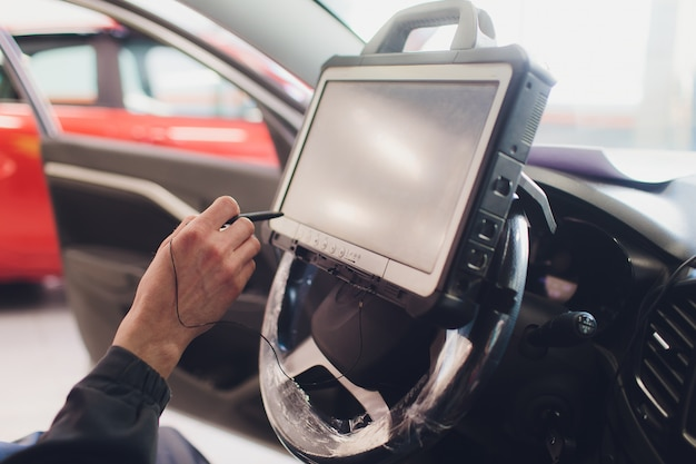 Mécanicien automobile entretient un véhicule à l'aide d'un ordinateur de diagnostic - technologie moderne dans l'atelier de réparation automobile.