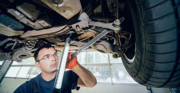 Mécanicien automobile examinant la suspension d'une automobile soulevée à une station-service de réparation