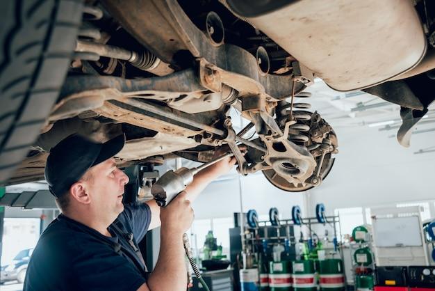 Mécanicien automobile inspectant la roue et la suspension des détails de l'automobile levée à la station-service de réparation