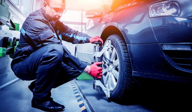 Mécanicien automobile installant un capteur pendant le réglage de la suspension.