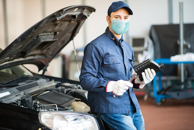 Mécanicien automobile masqué tenant une cruche d'huile moteur, concept de travail de coronavirus