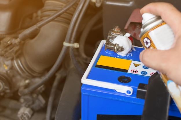 Mécanicien automobile avec outil de contrôle de fonctionnement et réparation d'un ancien moteur de voiture à la station-service