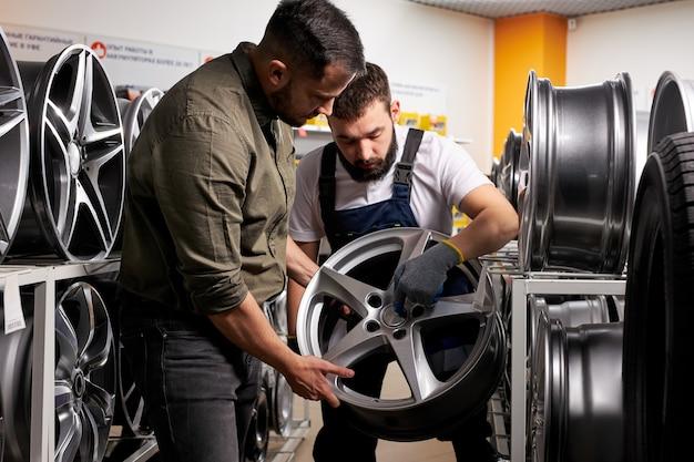 Mécanicien automobile parlant des caractéristiques et des avantages de la roue de voiture au client, ils ont une discussion. en magasin