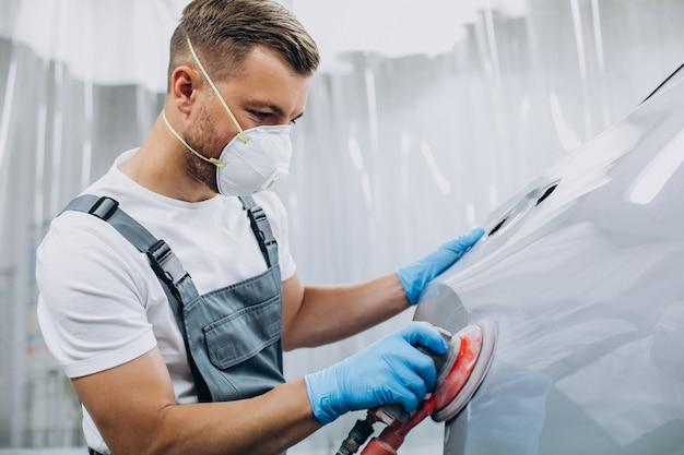 Mécanicien automobile polissant la voiture avant de peindre