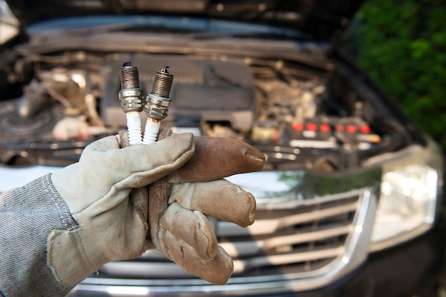 Mécanicien automobile portant des gants tenant de vieilles bougies d'allumage