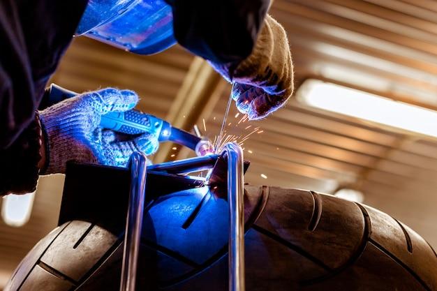 Mécanicien automobile professionnel travaillant dans le service de réparation automobile sur une découpeuse à gaz argon