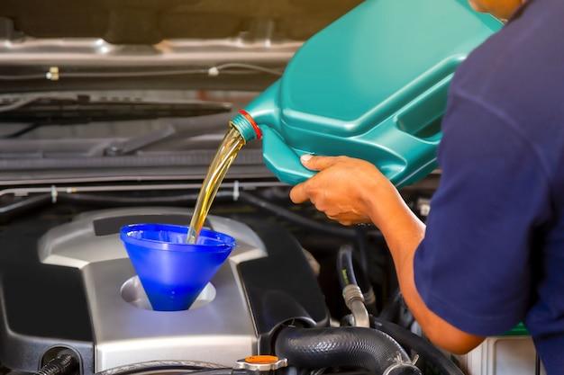 Un mécanicien automobile remplace et verse de l'huile neuve dans le moteur au centre de réparation et d'entretien