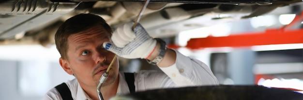 Mécanicien automobile réparant une voiture à la station de service de réparation