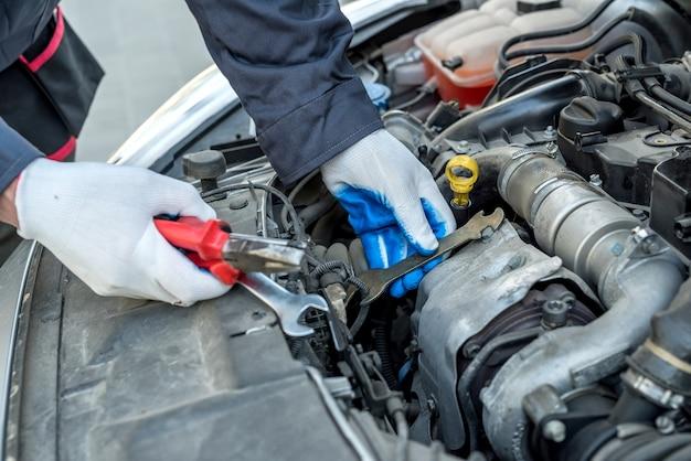 Mécanicien automobile en réparation automobile tenant la clé et les outils. diagnostic automobile