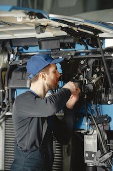 Mécanicien automobile répare la voiture bleue dans le garage avec des outils