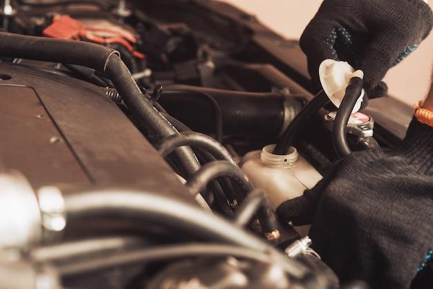 Le mécanicien automobile répare la voiture. l'employé effectue l'entretien de la machine.