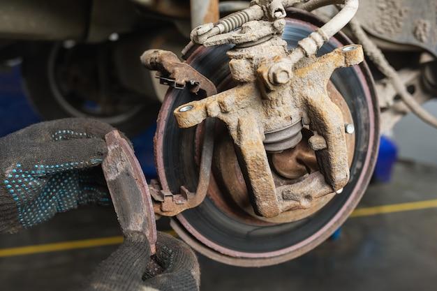 Un mécanicien automobile a retiré une plaquette de frein complètement usée
