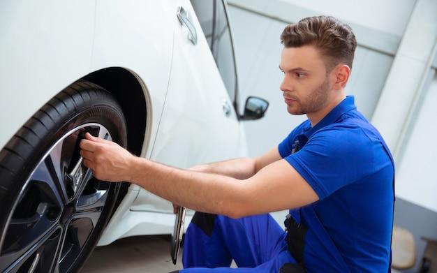 Le mécanicien automobile avec une tablette à la main et une combinaison de travail vérifie l'état des pneus après avoir changé