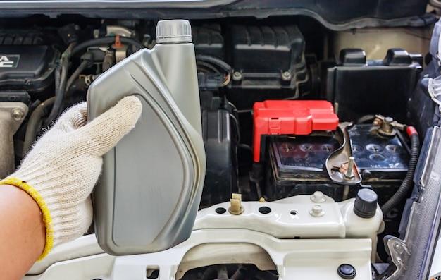 Mécanicien automobile tenant une huile de moteur, entretien de la voiture