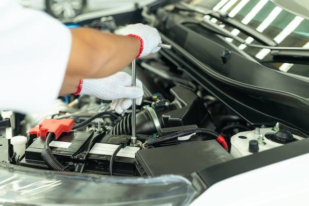 Mécanicien automobile travaillant dans un garage, centre de réparation automobile.