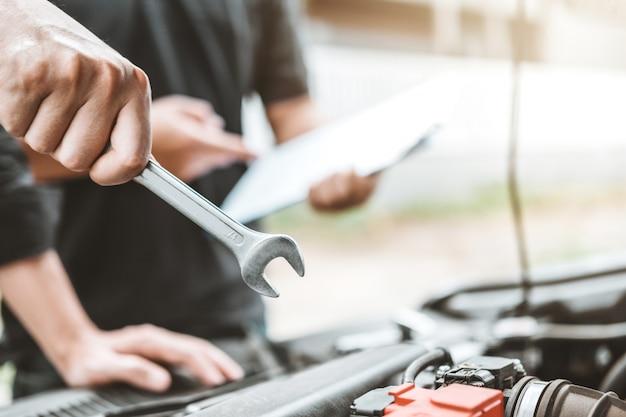 Mécanicien automobile travaillant dans un garage technicien mains de mécanicien automobile travaillant dans la réparation automobile