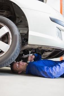 Mécanicien automobile travaillant sous la voiture