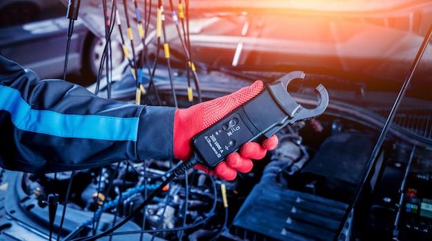 Le mécanicien automobile utilise un voltmètre pour vérifier le niveau de tension.