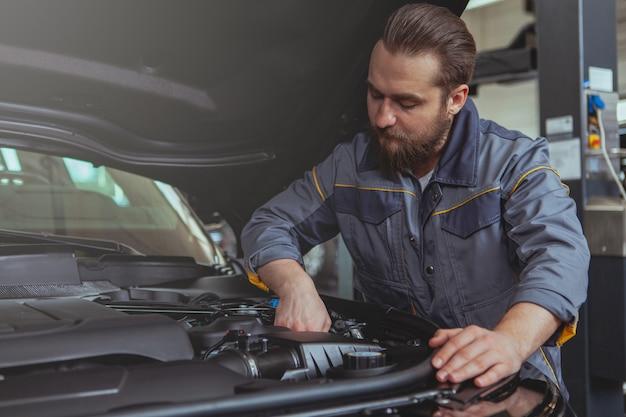 Mécanicien barbu travaillant à la station service de voiture