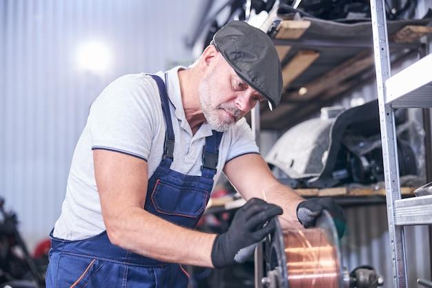 Mécanicien barbu utilisant du fil de cuivre à la station-service de réparation