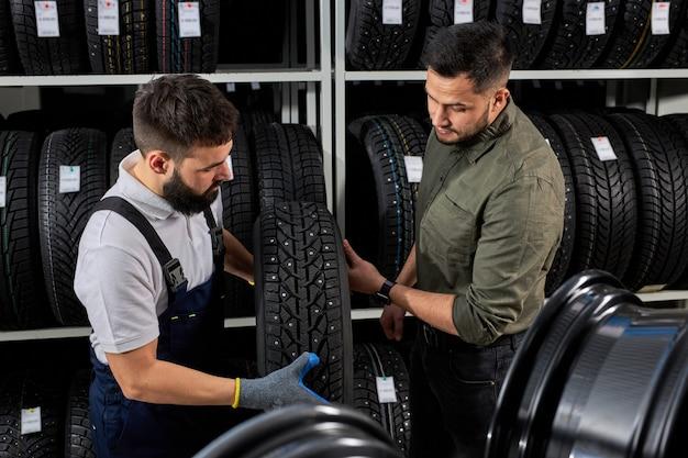 Mécanicien et client parlant de pneu au garage de réparation, le client de remplacement choisit le meilleur pour sa voiture