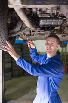 Mécanicien en combinaison travaillant sous la voiture