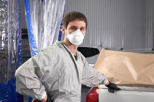 Mécanicien couvrant la voiture avant de peindre en service de réparation automobile