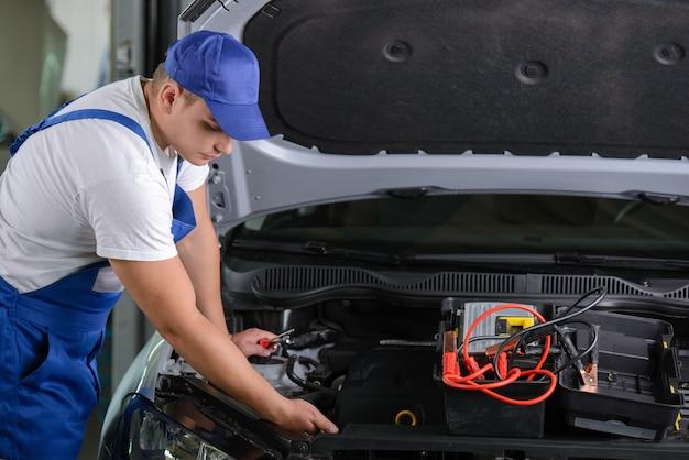 Mécanicien dans l'atelier debout à côté de la voiture avec capot ouvert.