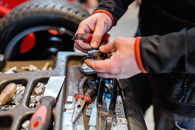 Mécanicien dans un atelier de voiture prenant des outils de travail à partir d'une armoire à outils