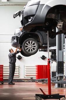 Mécanicien dépose la protection du moteur sur la voiture
