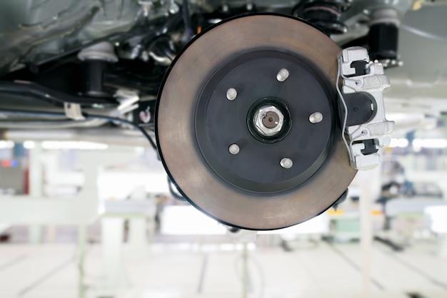 Mécanicien dévissant des pièces d'automobile en travaillant sous une auto levée