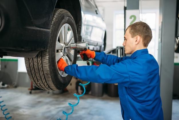 Le mécanicien dévisse la roue avec une clé pneumatique