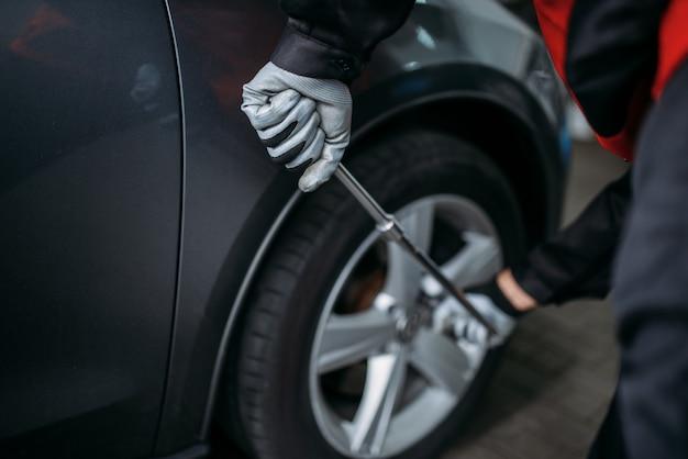 Mécanicien dévisse la roue en service de pneus