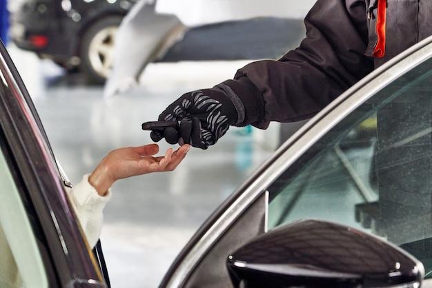Mécanicien donnant des clés de voiture à une cliente après l'entretien