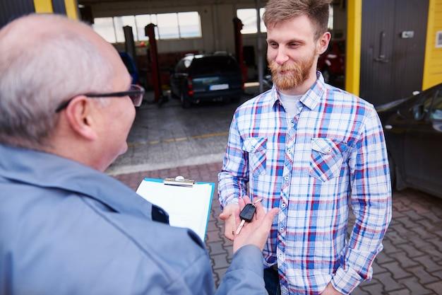 Mécanicien donnant la voiture des clés à un client