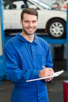 Mécanicien écrivant sur un bloc-notes au garage de réparation
