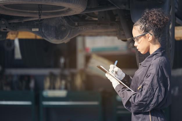 Mécanicien examinant le dessous au service de voiture, service de réparation automobile.