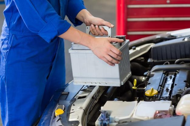 Mécanicien examinant sous le capot de la voiture