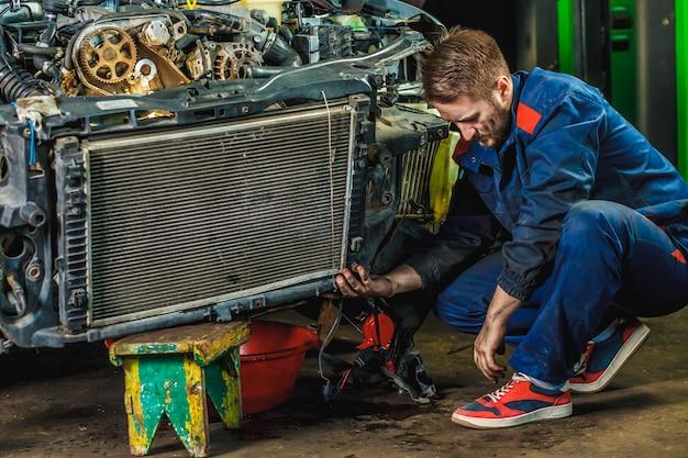 Un mécanicien fatigué dans une combinaison de protection bleue répare un radiateur de voiture. concept de service de réparation.
