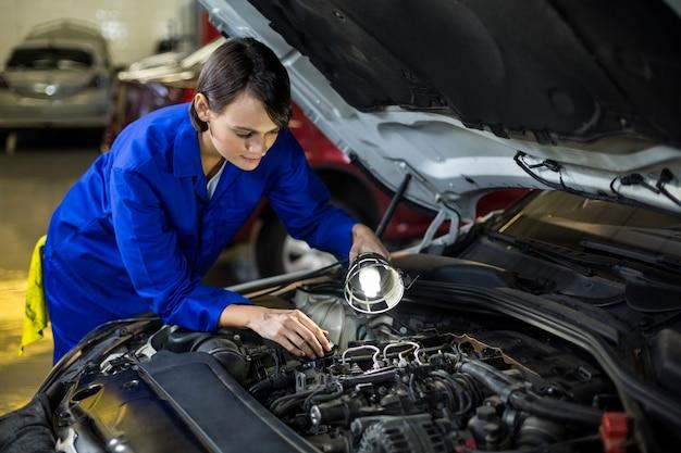 Mécanicien femme examinant un moteur de voiture avec lampe