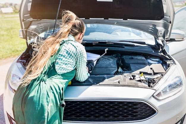 Mécanicien de femme examinant le moteur de voiture avec le presse-papiers