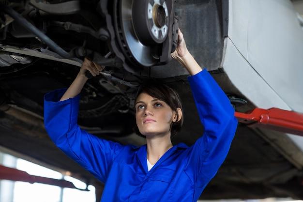 Mécanicien femme fixant un frein à disque de roue de voiture