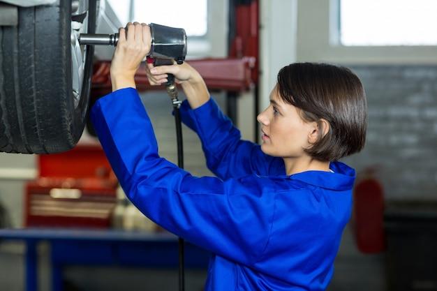 Mécanicien femme fixant une roue de voiture avec une clé pneumatique